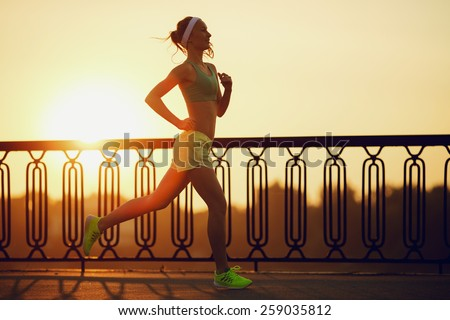 Running woman. Runner is jogging in sunny bright light on sunrise. Female fitness model training outside in the city on a quay. Sport lifestyle. - stock photo