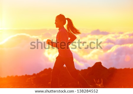Running - woman runner jogging at sunset. Fitness spot girl training in sunny sunshine with flare and sun glow. Aspirations workout image with asian jogger. - stock photo