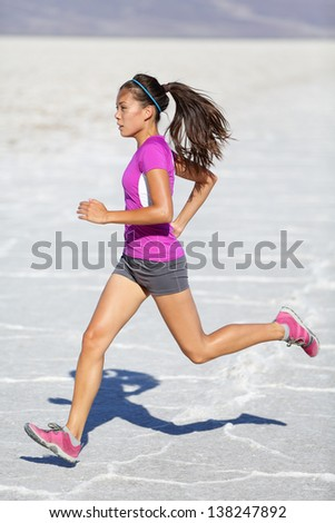 Running woman - runner sprinting on trail run in desert nature landscape. Female sport fitness athlete in high speed sprint in amazing desert landscape outside. Multiracial fit sports model sprinter. - stock photo