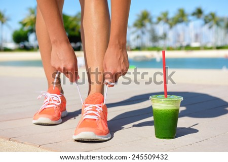 Running woman runner with green vegetable smoothie.  Fitness and healthy lifestyle concept with female model tying running shoe laces. - stock photo