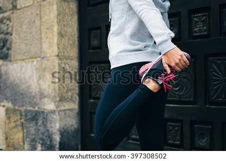 Running workout concept. Female athlete stretching for warming up before urban training. - stock photo