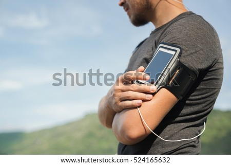 Running workout man listening to music with mp3 player armband or smart mobile phone.