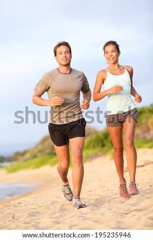 Running young mixed race couple jogging outside on beach happy smiling in summer sunset. Caucasian handsome male model and asian fitness female model.