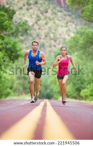 Running young mixed race couple sprinting concentrated on road outside in nature exercising jogging sport. Pretty asian model and caucasian male model. - stock photo
