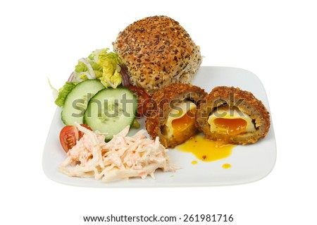 Runny yolk scotch egg bread roll and salad on a plate isolated against white - stock photo