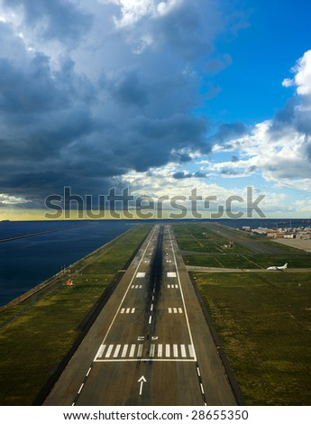 runway of an airport near the sea with cloudy sky above