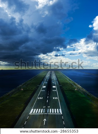 runway of an airport near the sea with cloudy sky above - stock photo