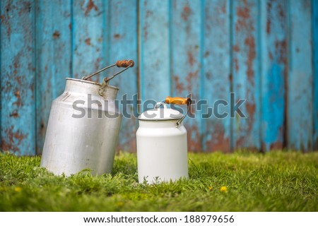 Rural background with vintage milk cans over grass and blue wooden background - stock photo
