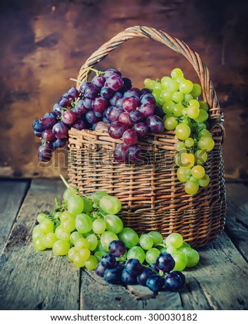 Rural Basket with Green and Red Grapes on Wooden Background. Country style - stock photo