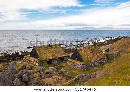 Rural beautiful summer landscape - fjord, houses with grass roofs, mountains. Iceland. - stock photo