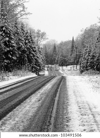 Rural country road during the first snowfall, done in black and white - stock photo