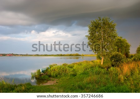 Rural dawn landscape with trees, lake and dark clouds - stock photo