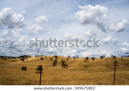 Rural drought landscape. Pastures in  autumn with yellow grass, wire fence and dramatic sky. Australia, NSW - stock photo