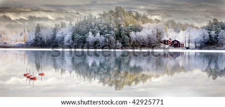 Rural house by a small hill reflected in the water in the early winter - stock photo