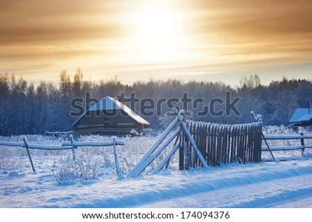 Rural house with a fence in winter - stock photo
