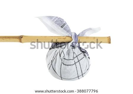 Rural knapsack on a bamboo pole isolated on white background - stock photo