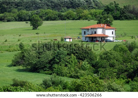 Rural landscape and lone white house in the Balkans - stock photo