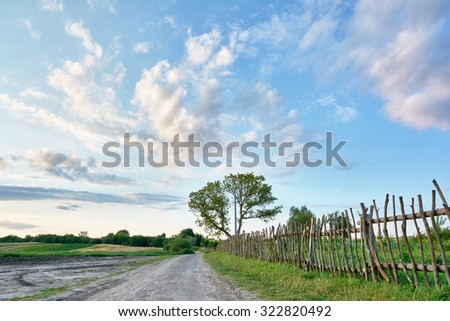 Rural landscape - dirt road, wooden fence, trees, fields, clouds in the blue sky - stock photo