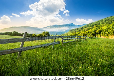 rural landscape. fence on the hillside meadow shot with ultrawideangle lense. forest in fog on the mountain top in morning light - stock photo