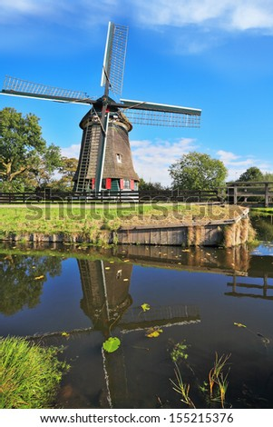 Rural landscape in the Netherlands. Verdant grove, quiet stream and a symbol of the country - Windmills