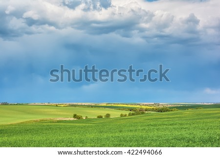 Rural landscape - meadows with thunderclouds over them. - stock photo