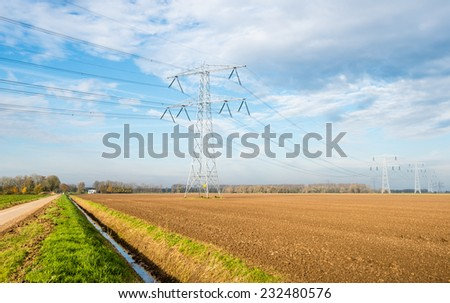 Rural landscape on a sunny day in autumn with a country road, a ditch and ploughed farmland with a row of power pylons. - stock photo