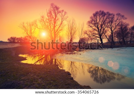 Rural landscape. Sunset over frozen lake. The beginning of spring - stock photo