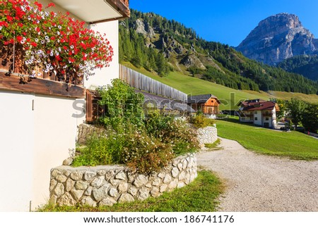 Rural landscape with alpine houses in Colfosco mountain village on sunny summer day, Dolomites Mountains, Italy - stock photo