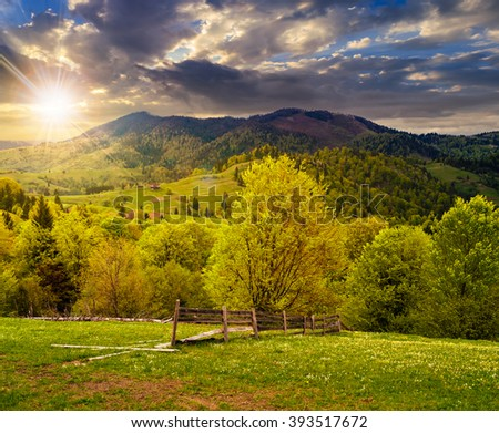 rural landscape with fence near the meadow and forest on the hillside in evening light - stock photo