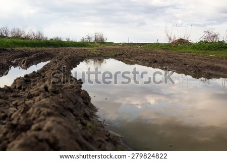 Rural landscape with green fields, soil texture, slops, beautiful sky and girl walking