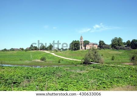 Rural landscape with hills, river, a village and christian church ruins far away on sunny summer day