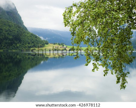 Rural landscape with houses, mirror reflection in the water, Norway - stock photo
