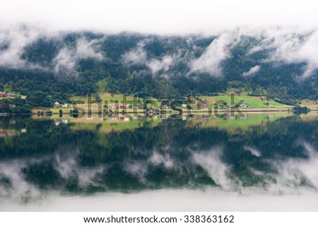 Rural landscape with houses, waterfall and clouds, mirror reflection in the water, Norway - stock photo