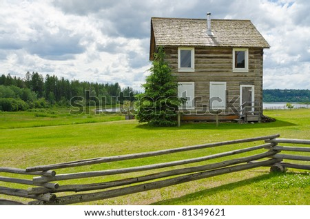 Rural landscape with lush green field and old house over a tranquil lake view. - stock photo
