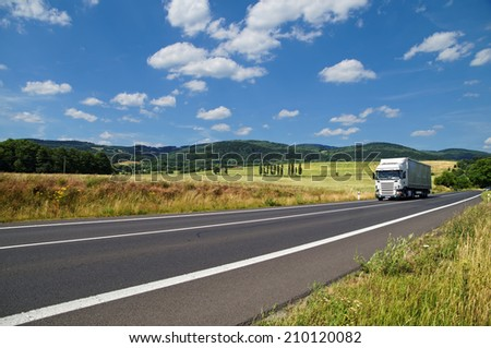 Rural landscape with road you are driving a white truck, in the background of a green cornfield and wooded mountains - stock photo