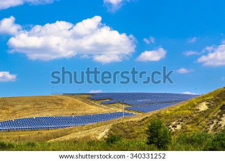 Rural landscape with solar panels, blue sky and white clouds. - stock photo