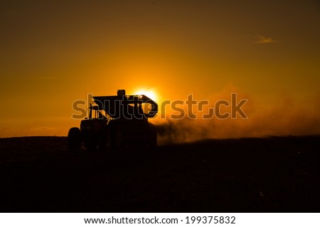 Rural machine working at agriculture field at sunset. - stock photo