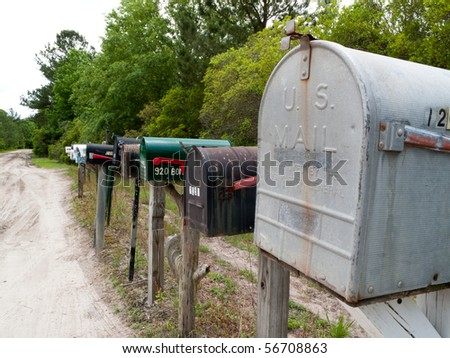 Rural mailboxes lined up along a dirt country road.. - stock photo
