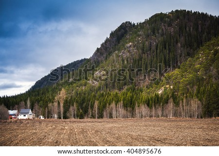 Rural Norwegian landscape with wooden houses and clouds over mountains - stock photo