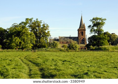 Rural parish church framed between old oak trees at the end of a footpath through a field. - stock photo