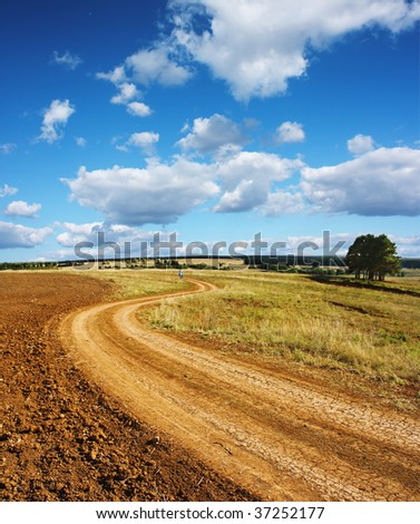 Rural road and blue sky with clouds - stock photo