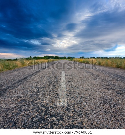Rural road before thunderstorm - stock photo