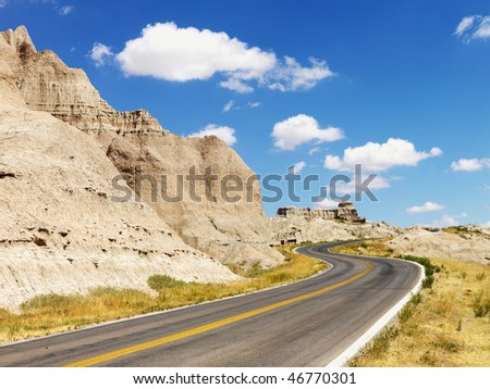 Rural road by rock formations and a field in Badlands National Park, South Dakota. Horizontal shot. - stock photo