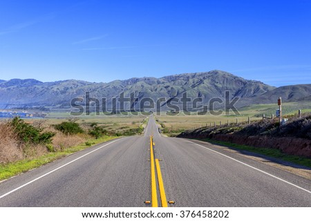 Rural road & coastal hills / mountains, blue sky, white clouds, & green meadow. Traveling the Big Sur Highway (Highway 1), California Central Coast..  - stock photo