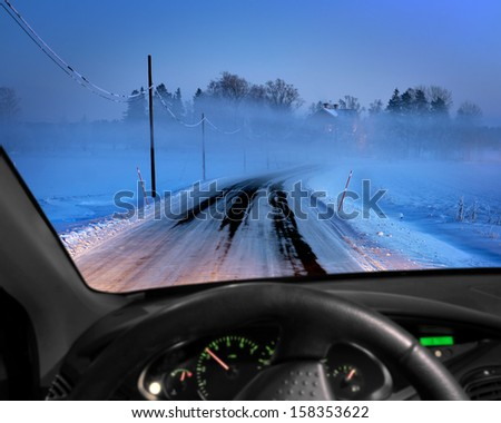 Rural road in cold foggy winter evening seen through windscreen of car - stock photo
