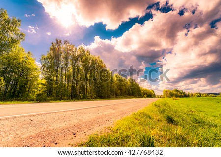 Rural road passing through fields and woods illuminated by the sun. View from the side of the road, image in the soft orange-purple toning - stock photo