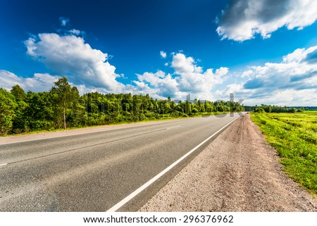 Rural road passing through fields and woods. View from the road - stock photo