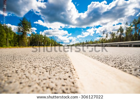 Rural road passing through the forest. View from the level of the dividing line - stock photo