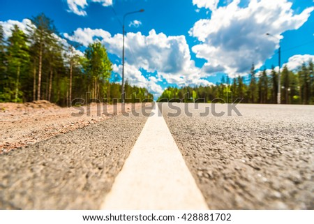 Rural road passing through the forest. View from the level of the dividing line, focus on the asphalt - stock photo