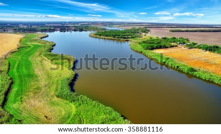 Rural, rustic landscape with river and wheat fields in summer day.  - stock photo